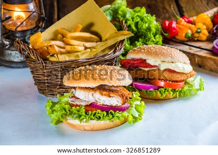 Juicy and tasty looking fish burger with fried potatoes - stock photo
