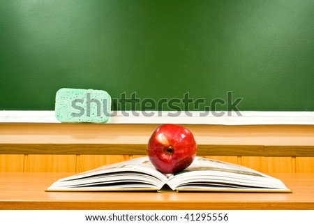 juicy apple and book at school on a background a board - stock photo
