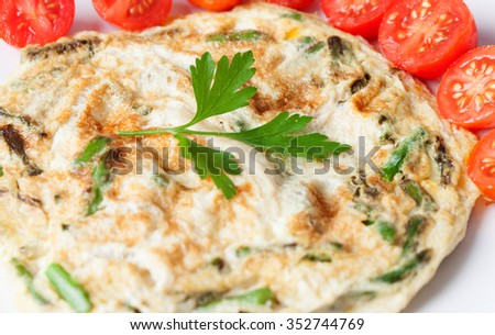 Juicy asparagus omelette surrounded by small tomatoes - stock photo