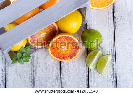 Juicy assortment of citrus fruits on white wooden background - stock photo