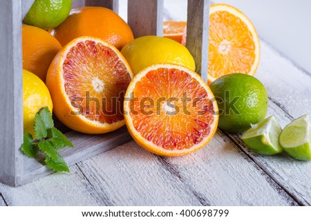 Juicy assorttment of citrus fruits on white wooden background - stock photo