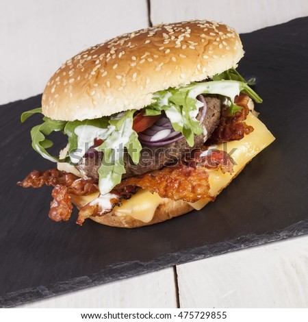 juicy  bacon cheese bbq burger on wooden table with fries