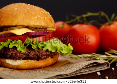 Juicy beef burger with fresh lettuce, sliced tomato and pickle, and a piece of cheese on a wooden board.