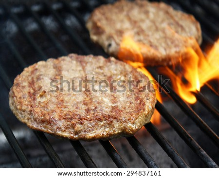 Juicy beef burgers sizzling over hot flames on the barbecue