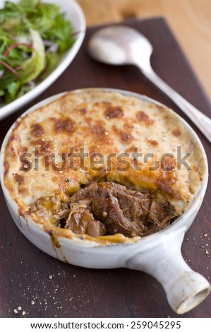 Juicy beef pot pie in a white oven pot, with salad to the top left and a spoon the the top right, all sitting on a dark wood chopping board which has pepper sprinkled on it and the pie. - stock photo