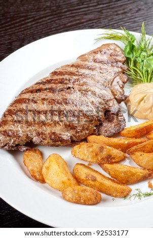 Juicy beef steak stuffed with beef tongue and cheese served with potatoes, greenery and sauce - stock photo