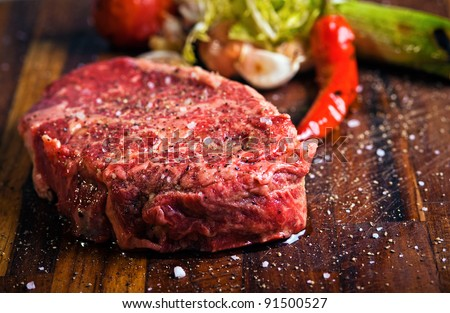 Juicy  beef steak with pepper on a butcher block - stock photo