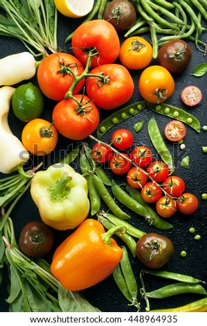 Juicy bright summer vegetable background. Multicolored tomatoes, peppers, young peas, green beans, spinach and other vegetables and herbs on a black background.   Vegan concept - stock photo