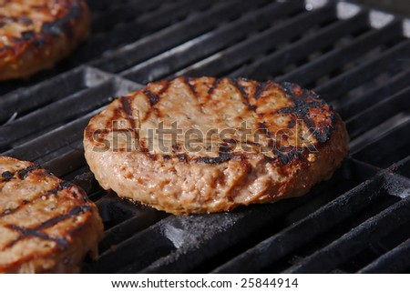 Juicy burger grilling on a hot barbecue. - stock photo