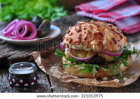 juicy burger with beef, cheese, lettuce, sour cucumber, pickled onions and cheese loaf - stock photo