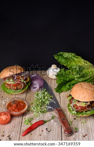 Juicy burgers with ingredients: salad, mushrooms, onion, beef, pepper and tomato sauce over wooden table. Black background and copy space. - stock photo