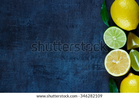 Juicy citrus fruits with leaves on dark vintage background. Agriculture, Gardening, Harvest Concept. Rustic background layout with free text space. Top view. - stock photo
