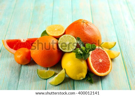 Juicy composition of citrus fruits on wooden background