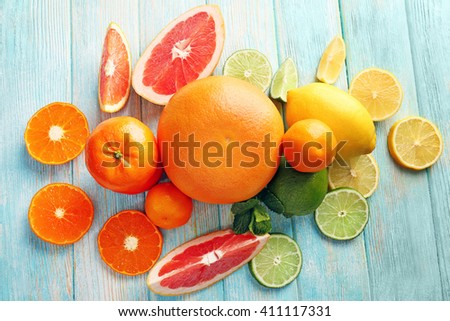 Juicy composition of tropical fruits on wooden background - stock photo