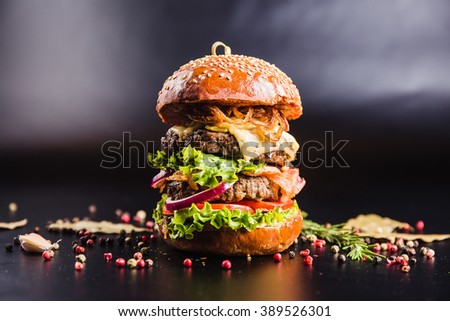 Juicy delicious burger with spices on a black background - stock photo