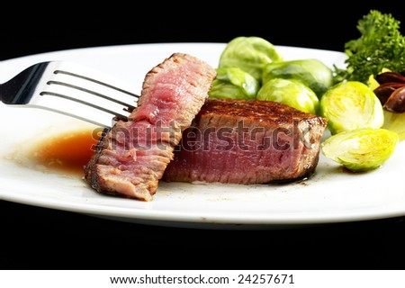 juicy filet mignon on plate with brussel sprout over black background - stock photo