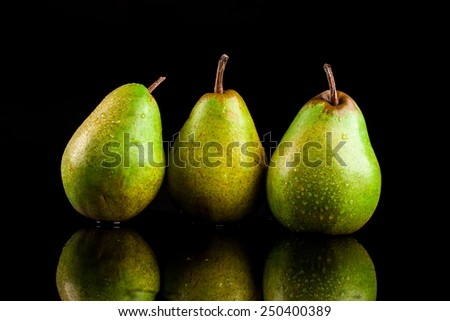 Juicy flavorful pears on a black background - stock photo