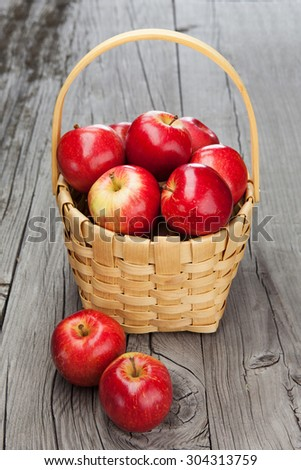 Juicy fresh apples in basket on dark wooden background. Harvest time