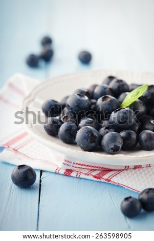 Juicy fresh blueberries in a white plate on blue wooden background, selective focus - stock photo