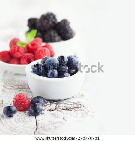 Juicy fresh blueberries, raspberries and blackberries in a white plate on old wooden background, selective focus - stock photo