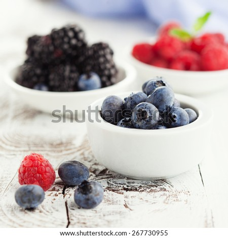 Juicy fresh blueberries, raspberries and blackberries in plates on white wooden background, selective focus - stock photo