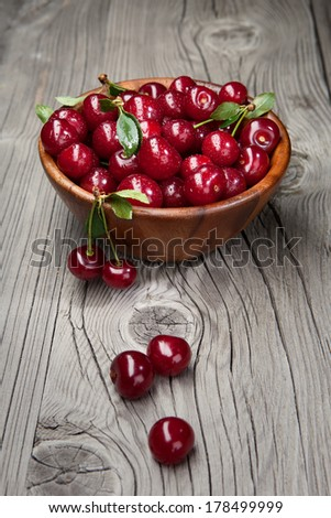 Juicy fresh cherries with leaves in dark bowl on old wooden background - stock photo
