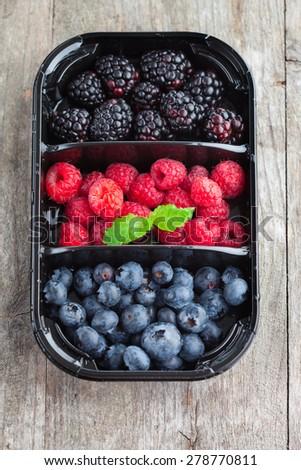 Juicy fresh raspberries, blackberries and blueberries on old wooden background, top view - stock photo