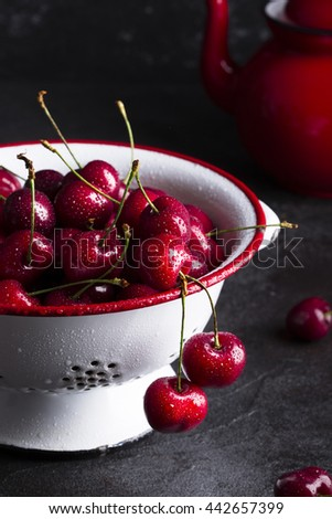Juicy fresh red cherries on a dark background in a white plate - stock photo