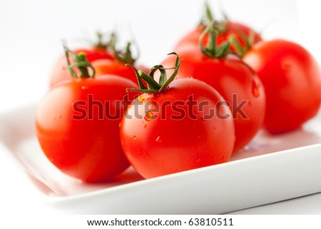 Juicy, fresh red tomatoes on a white plate