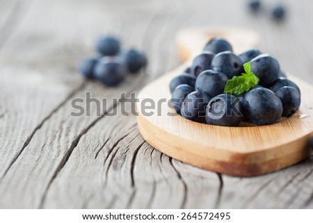 Juicy fresh ripe blueberries on old wooden background, selective focus - stock photo