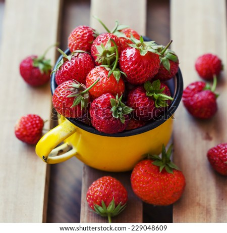 Juicy fresh ripe red strawberries on wooden table top - stock photo