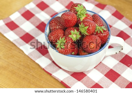 Juicy, fresh strawberries in a cup on the table.