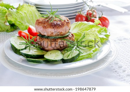Juicy fried meat cutlets with rosemary,salad and tomatoes - stock photo