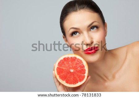 Juicy fruit! A close-up of a pretty lady's face with a fresh luscious grapefruit. - stock photo
