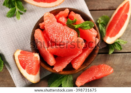 Juicy grapefruit pieces with fresh mint in a bowl, close up - stock photo