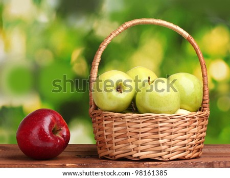 juicy green apples in basket and red apple on wooden table on green background