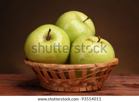 green and red apples in basket. juicy green apples in basket on wooden table brown background and red j