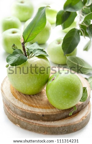 Juicy Green Apples on a white table with wooden stand - stock photo
