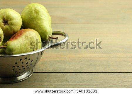 juicy green pears are in the strainer on wooden brown background - stock photo