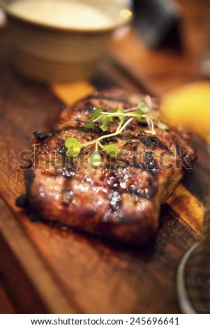Juicy grilled beef steak on a wooden plate - stock photo