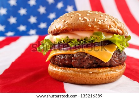 Juicy grilled hamburger on USA flag background - stock photo