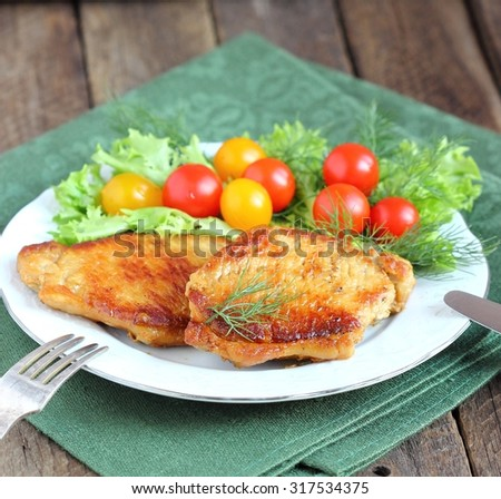 juicy grilled pork chop with greens and tomatoes
