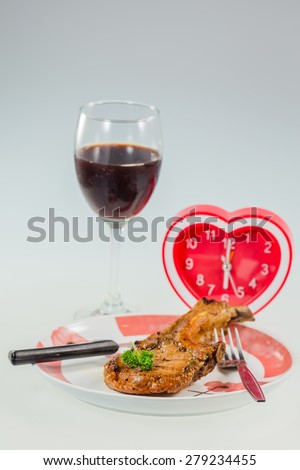 juicy grilled pork chop with Heart Clock,Drink Wine for dinner time - stock photo