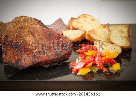Juicy grilled steaks served with roasted potatoes and peppers on black granite board, vignetted - stock photo