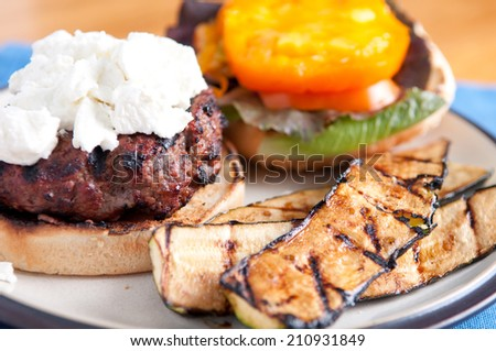 juicy hamburger with goat cheese, tomato and lettuce with grilled zucchini on the side - stock photo