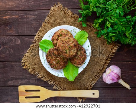 Juicy homemade cutlets (beef, pork, chicken) on a wooden background. For a hamburger. The top view. - stock photo