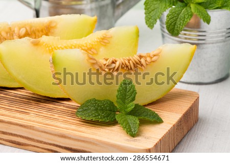 Juicy honeydew melon on a wooden table background. - stock photo