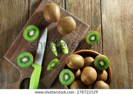Juicy kiwi fruit with knife on cutting board on wooden background - stock photo
