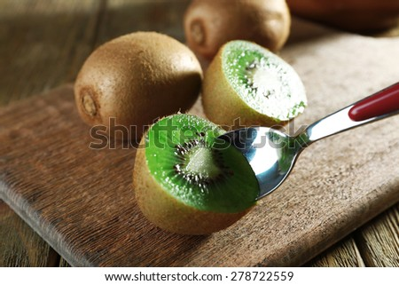 Juicy kiwi fruit with spoon on cutting board on wooden table - stock photo