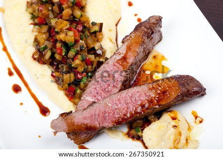 juicy lamb fillet with polenta, gravy, and vegetables of aubergine, sweet pepper, zucchini - stock photo